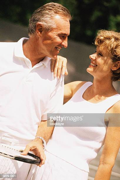 Man and woman wearing tennis outfits, smiling