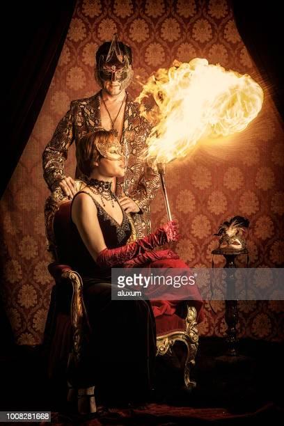 hombre y mujer usando máscaras venecianas y escupiendo fuego - faquir fotografías e imágenes de stock