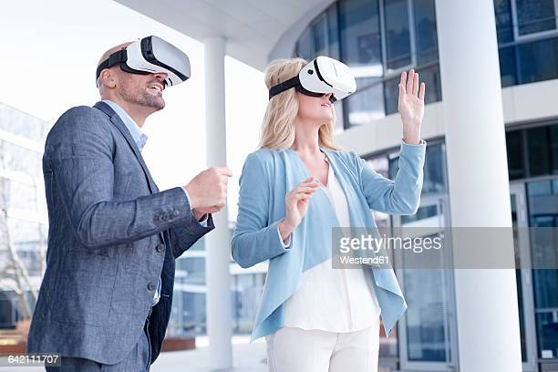 Man and woman wearing virtual reality glasses outdoors