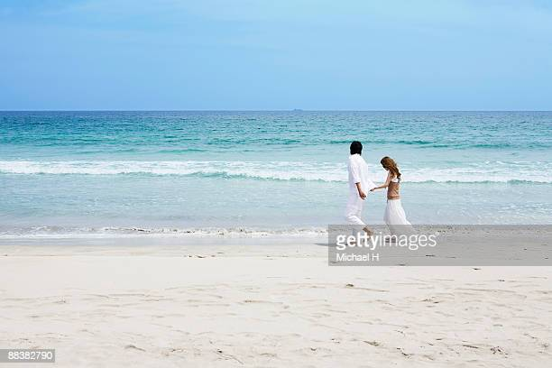 Man and woman who strolls on beach