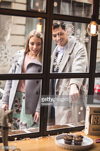 Man and woman window shopping for cupcakes