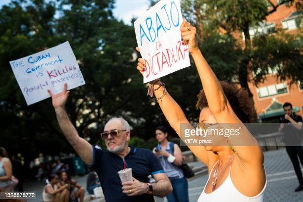 Man and woman with banners rally in support of Cuban protesters in Union Square Park on July 14, 2021 in New York City. A small group of people...