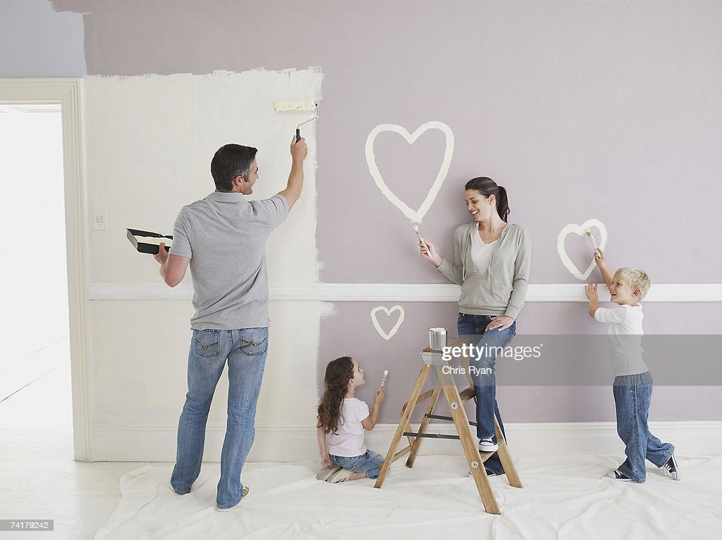 Man and woman with boy and girl painting hearts on wall : Stock Photo