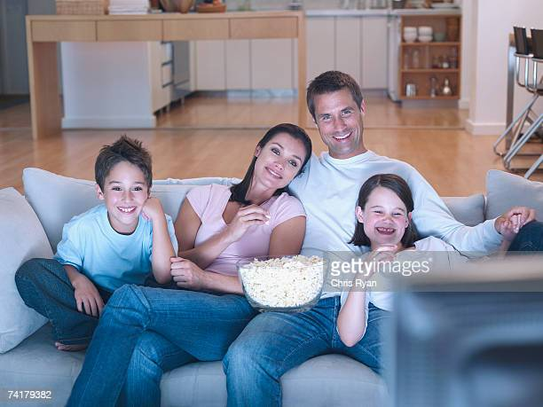 Man and woman with boy and girl watching television and eating popcorn