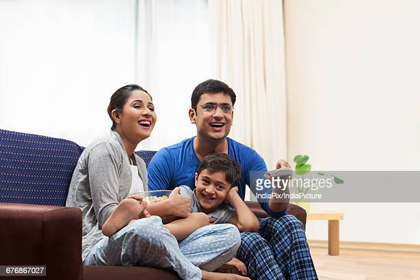 man and woman with boy watching television and eating popcorn - indian subcontinent ethnicity stock pictures, royalty-free photos & images