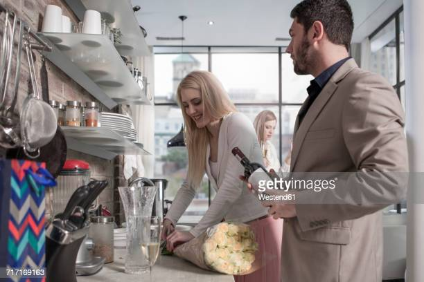 man and woman with bunch of flowers and wine bottle in kitchen - gift lounge stock-fotos und bilder