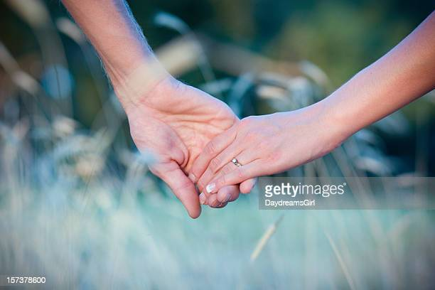 Man and Woman with Diamond Ring Couple Holding Hands Outdoors
