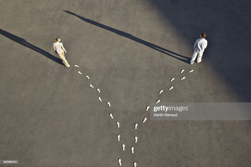 Man and woman with diverging line of footprints : Stock Photo