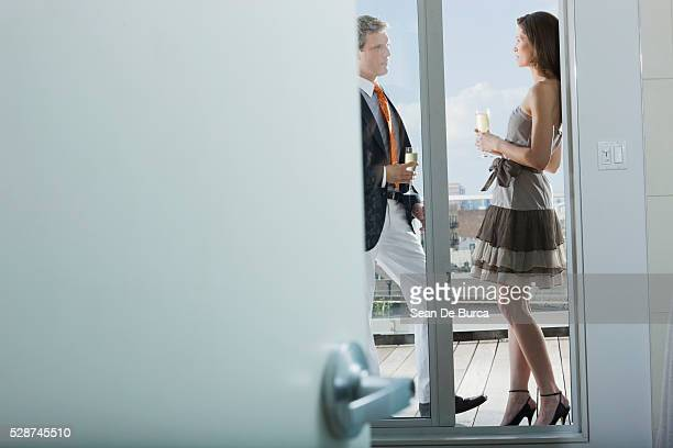Man and Woman with Drinks on Balcony