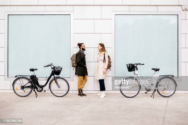 man and woman with e-bikes standing at a building talking - cara a cara imagens e fotografias de stock