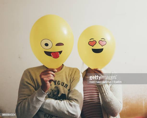 Man And Woman With Face Covered By Balloons Against Wall
