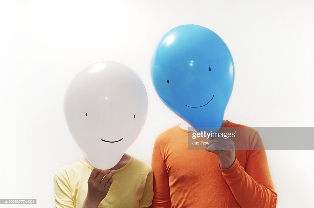 Man and woman with faces obscured by faced balloons : Foto de stock