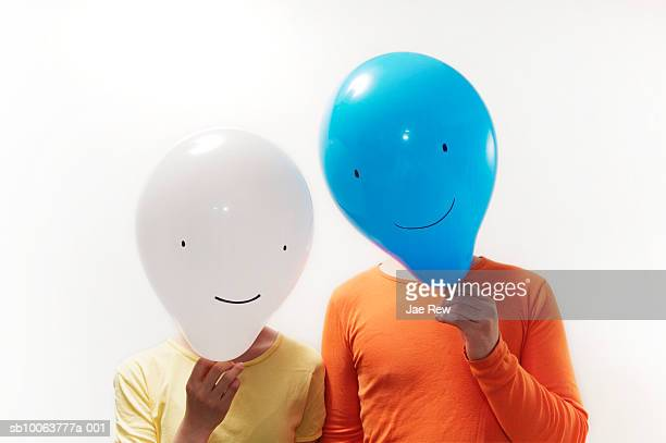 Man and woman with faces obscured by faced balloons