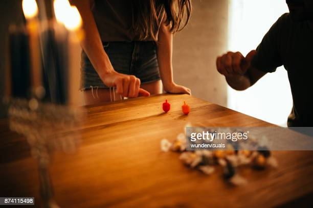 man and woman with menorah playing dreidel game on hannukah - dreidel stock photos and pictures