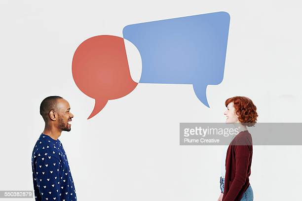man and woman with overlapping speech bubbles - comunicazione foto e immagini stock