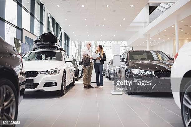 Man and woman with paper standing amidst cars at showroom