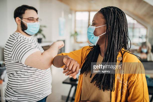 man and woman with protective masks greeting with elbows in office - elbow bump stock pictures, royalty-free photos & images