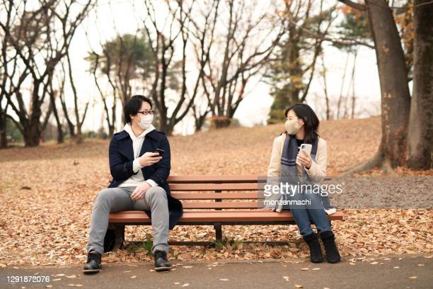 man and woman with smart phone talking in keeping social distance - saitama prefecture stock pictures, royalty-free photos & images