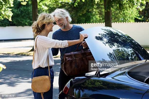 man and woman with standing by car - robin skjoldborg stock pictures, royalty-free photos & images
