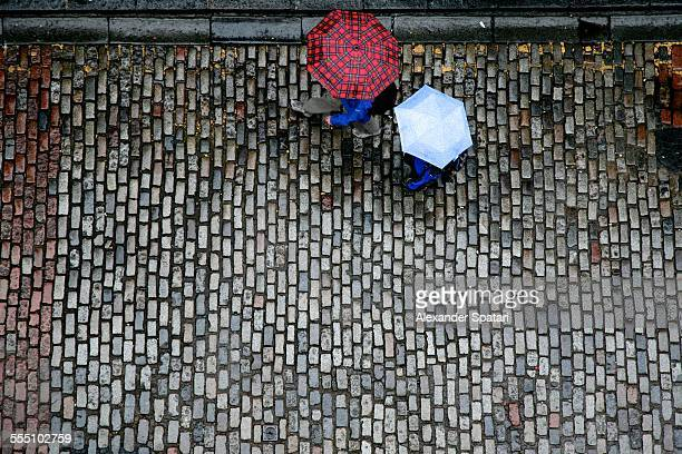 Man and woman with umbrellas on a cobbled street