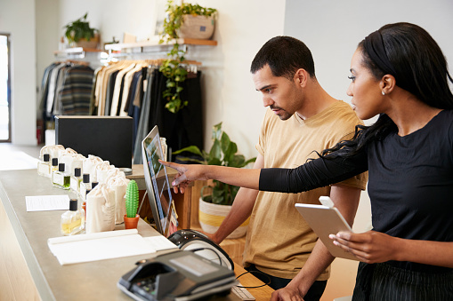 Man and woman working behind the counter in a clothing store 901863898