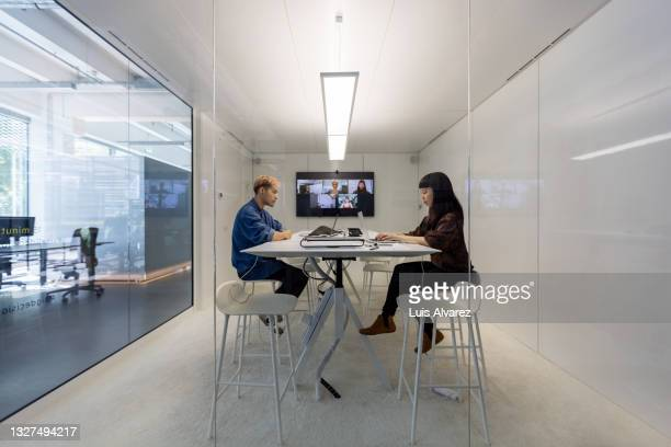 man and woman working in hybrid office cubicle - remote location stock pictures, royalty-free photos & images