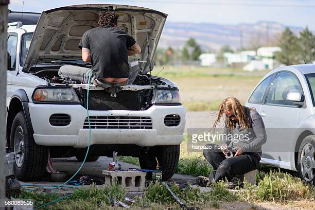 man and woman working on a vehicle. - builders bum stock pictures, royalty-free photos & images