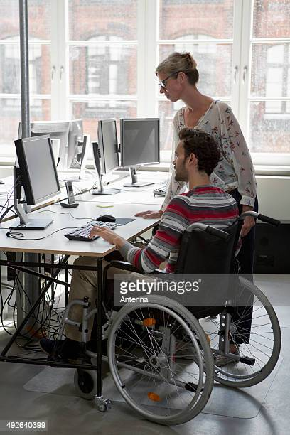 man and woman working on computer in office - leaning disability stock pictures, royalty-free photos & images