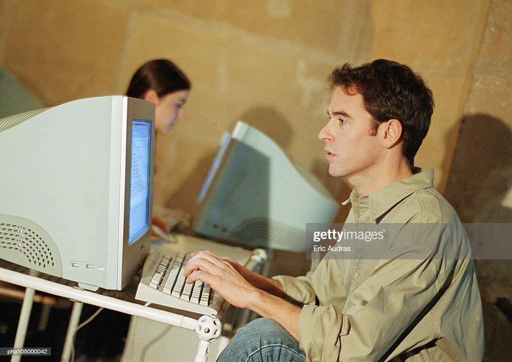 Man and woman working on computers in office : Stockfoto
