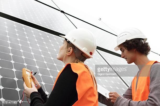 man and woman working on photo voltaic panels - sigrid gombert stock-fotos und bilder