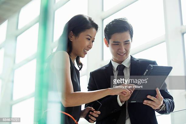 Man and woman working together, modern office