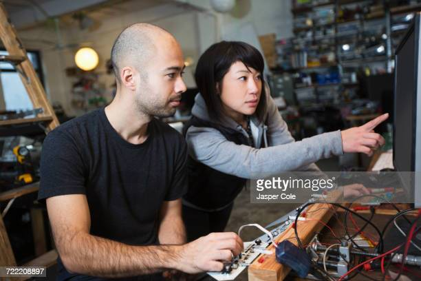 Man and woman working with electronics in workshop