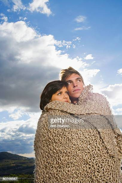 Man and woman wrapped in blanket.