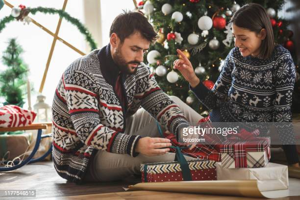man and woman wrapping christmas presents - donna bendata foto e immagini stock