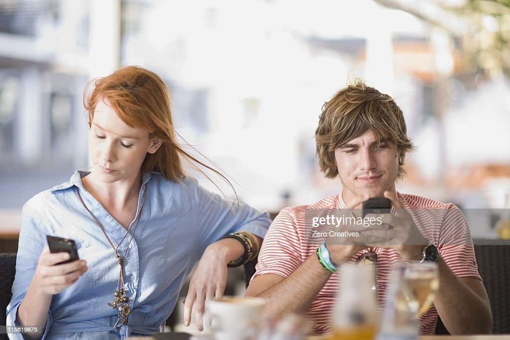 Man and woman writing sms : Stock Photo