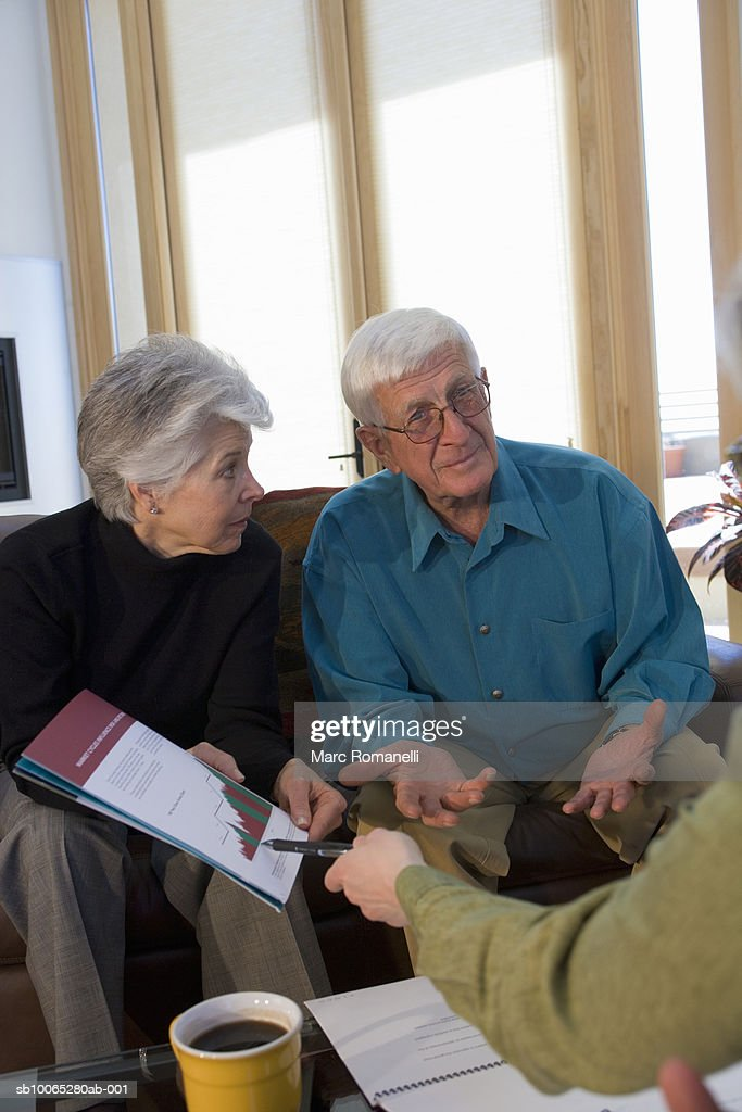 Man and women discussing graph around table : Foto stock