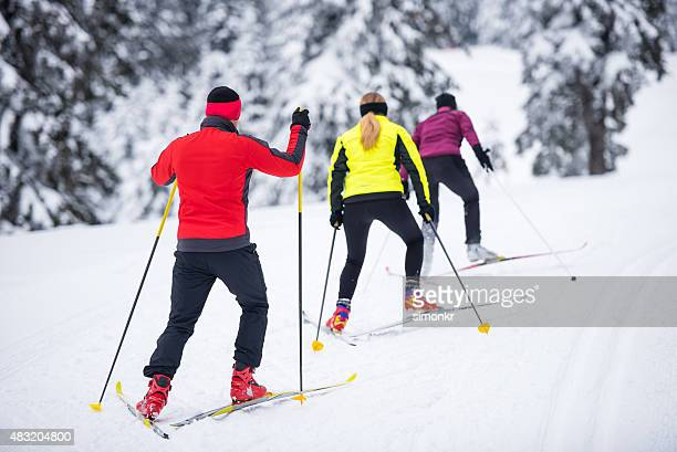 man and women enjoying skiing - langlaufen stockfoto's en -beelden