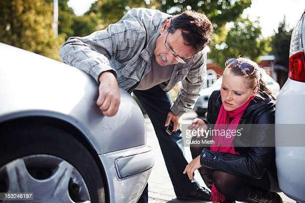 Man and women examining a car