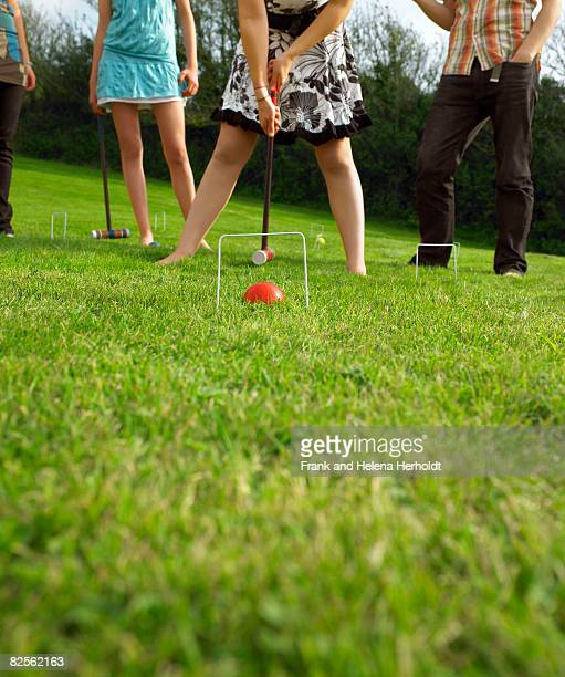 Man and women playing croquet in garden