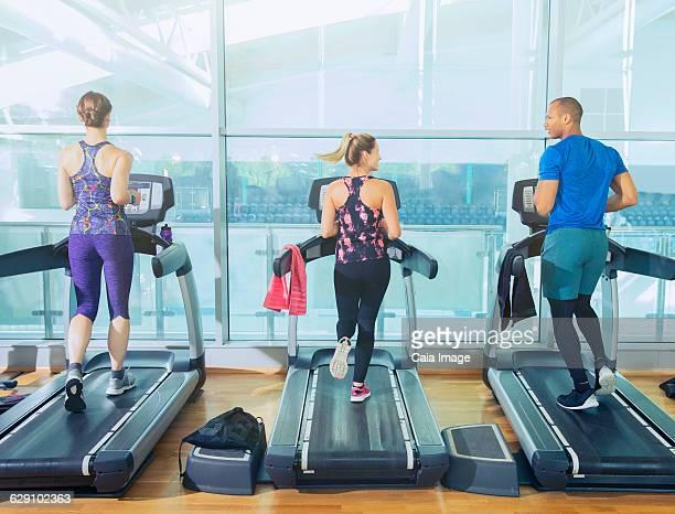 Man and women running on treadmills at gym