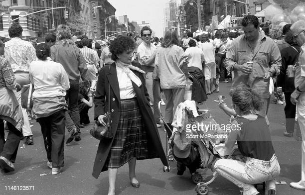 A man and women stand by as a second woman couches beside a stroller among a crowd on 9th Avenue in Hell's Kitchen during the International Food...