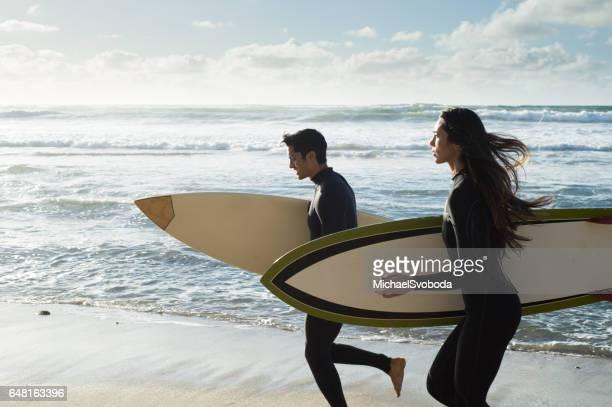 Mann und Frau Surfer auf dem Wasser laufen