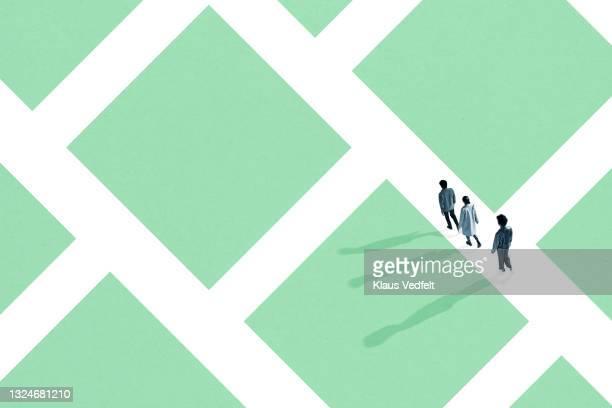 man and women walking in green maze - carré forme bidimensionnelle photos et images de collection