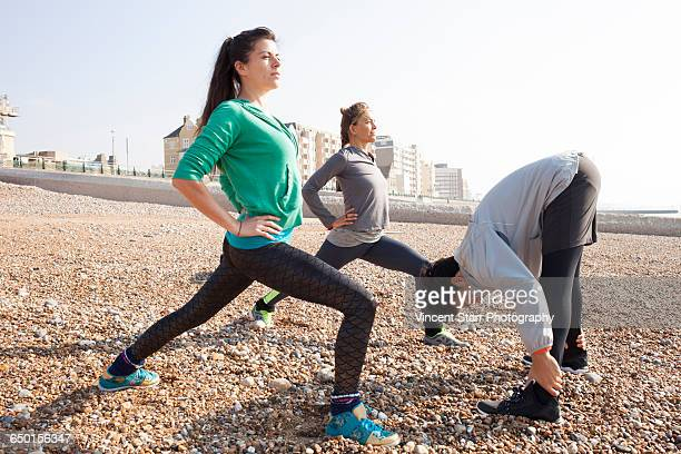 Man and women warm up training, stretching on Brighton beach