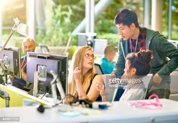 Man and women working at desk in modern office.