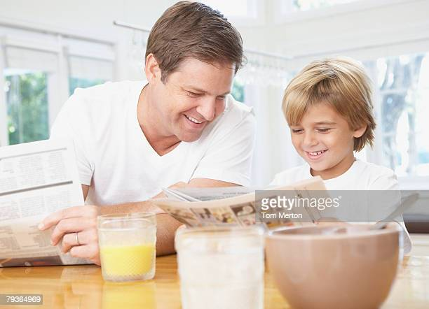 Man and young boy in kitchen reading newspaper