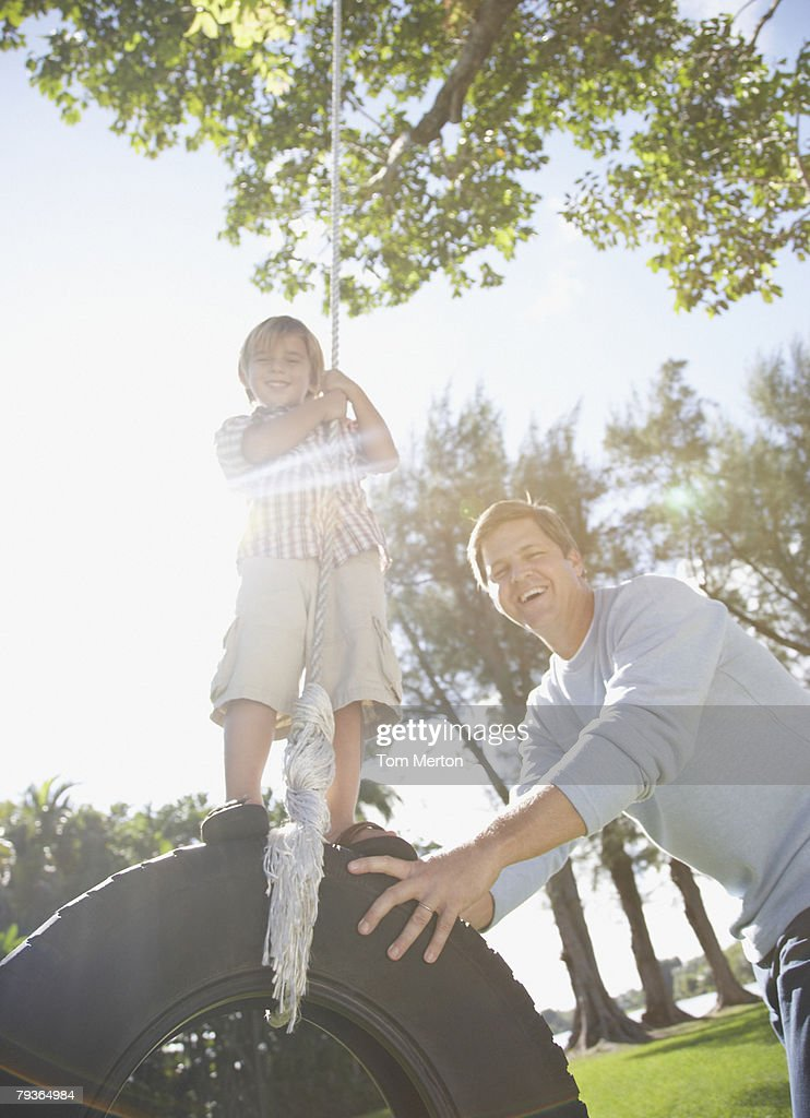 Man and young boy outdoors at park playing on tire swing : Stock Photo