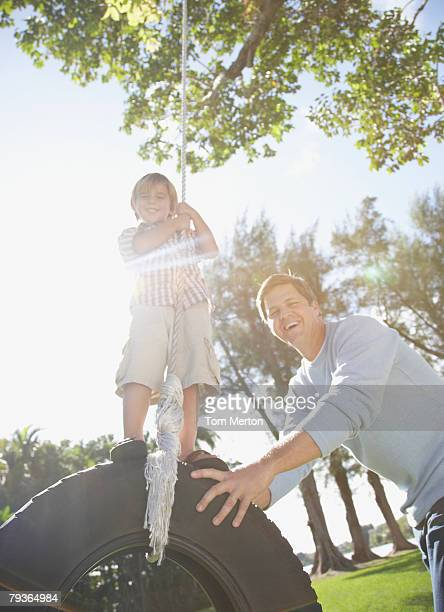 Man and young boy outdoors at park playing on tire swing
