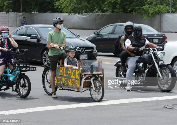Man and young boy ride a bicycle with a Black Lives Matter sign attached as protest against police brutality and racism take place on June 6, 2020 in...