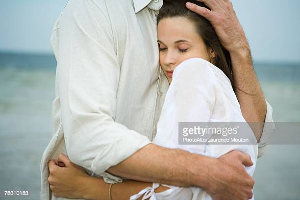 man and young female companion embracing, close-up - beschützer stock-fotos und bilder